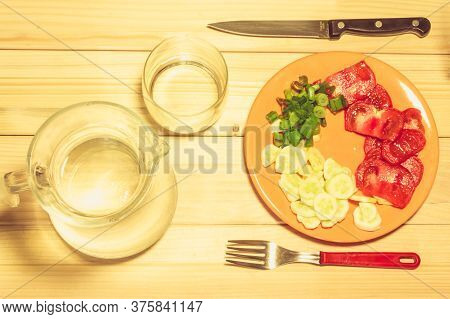 A Few Sliced Vegetables On A Plate Next To A Fork, A Knife, An Empty Glass And A Pitcher Full Of Wat