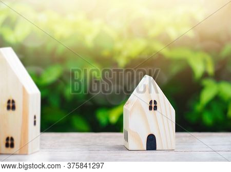 Wood House Model On Wooden Table With Green Nature Blur Background And Sunray. Savings Plans For Hou