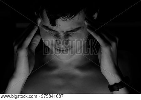 Portrait Teenager On A Black Background. Concept Of Pain And Tension