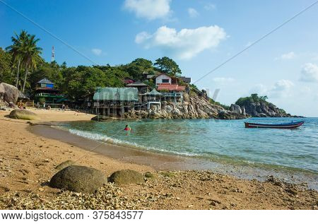 Coral sand on small Sai Nuan beach on tropical island Koh Tao, Popular destination for travel holidays in Thailand. Bungalows on cliff and boat on water