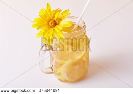 Glass Pitcher With Cold Refreshing Beverage Decorated With Flower, Cocktail With Lemon Slices And Dr