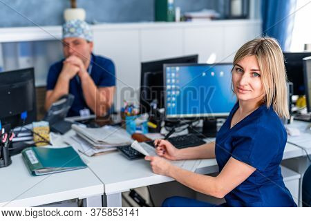 Two Doctors Discussing Medical Expertise In Office At Computer. Man And Woman Medics.