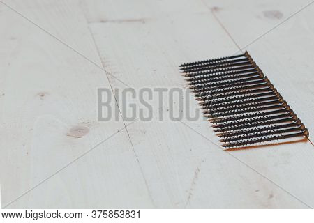 Flat Lay Metal Thin Nails On A Light Wooden Background, Place For Text, Construction Concept
