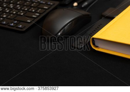 Composition With Black Pen, Computer Keyboard, Smartphone, Leather Wallet And Bright Yellow Notebook