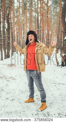 Handsome Man Standing And Singing In Forest In Winter Season. Young Male Wearing Beige Jacket Over R