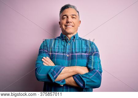 Middle age handsome grey-haired man wearing casual shirt over isolated pink background happy face smiling with crossed arms looking at the camera. Positive person.