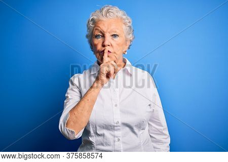 Senior beautiful woman wearing elegant shirt standing over isolated blue background asking to be quiet with finger on lips. Silence and secret concept.