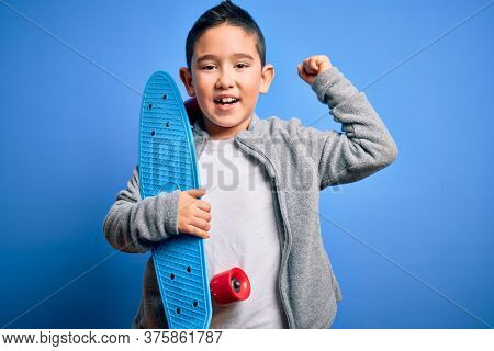 Young little boy kid skateboarder holding modern skateboard over blue isolated background screaming proud and celebrating victory and success very excited, cheering emotion