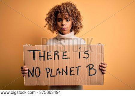 African american activist woman asking for environment holding banner with planet message with a confident expression on smart face thinking serious