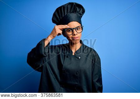 Young african american chef woman wearing cooker uniform and hat over blue background worried and stressed about a problem with hand on forehead, nervous and anxious for crisis