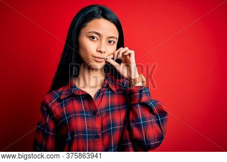 Young beautiful chinese woman wearing casual shirt over isolated red background mouth and lips shut as zip with fingers. Secret and silent, taboo talking