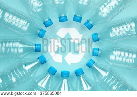 Horizontal Color Image With An Overhead View Of A Clear Plastic Bottles With Caps On A Blue Backgrou