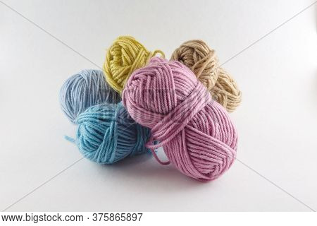 Multi-colored Skeins Of Woolen Threads Of Light Background. Different Sizes. Set Of Colorful Rolls O