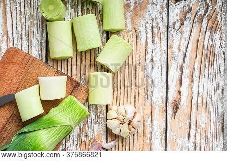 Green Chopped Leek Sultan On Choppong Board Over White Wood Table Top View With Space For Text.