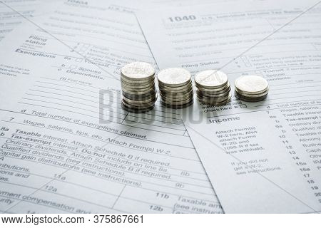 1040 Us Tax Forms With Coins. Taxation Concept
