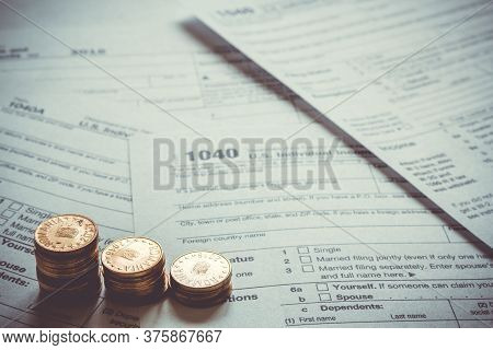1040 Us Tax Form With Coins. Taxation Concept.cr2