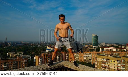 A Smart Guy Shirtless Standing On A Parapet Of The Roof Of The Building At The Dawn Against The Back