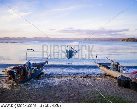 Fisherman With Traditional Boat Returns To The Coast After A Fishing Trip, Bolsena Lakeshore, Viterb