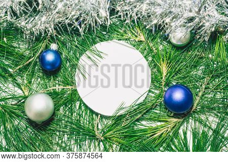 X-mas Background With Silver Decoration, Christmas Balls And Green Pine Leaves. Round Copy Space For