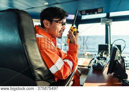 Filipino Deck Officer On Bridge Of Vessel Or Ship. He Is Speaking On Gmdss Vhf Radio