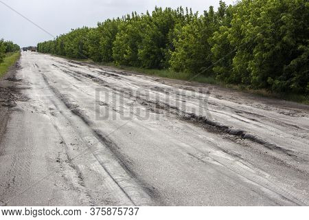 Poor Condition Of The Road Surface. Spring Season. Hole In The Asphalt, Risk Of Movement By Car, Bad