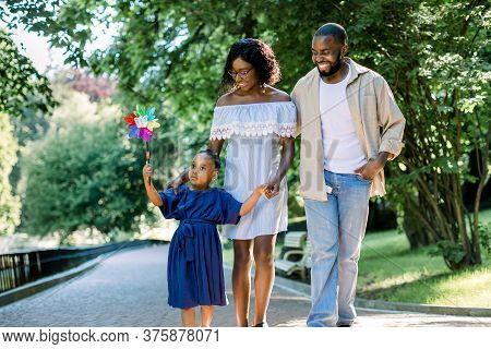 Happy Family, Joyful Time Together Outdoors. Dark Skinned Little Girl In Blue Dress, Blowing Colorfu