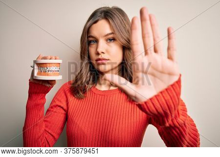 Young blonde girl holding orthodontist prosthesis denture over isolated background with open hand doing stop sign with serious and confident expression, defense gesture