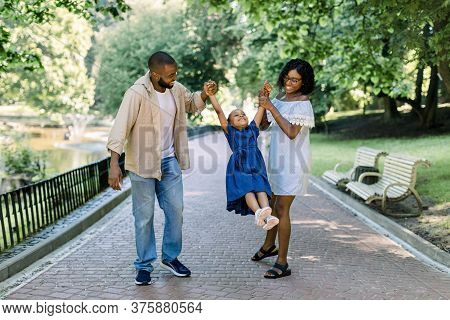 Happy African Family In The Park In The Summer Sunny Evening. Mom, Dad And Happy Daughter Walk At Su