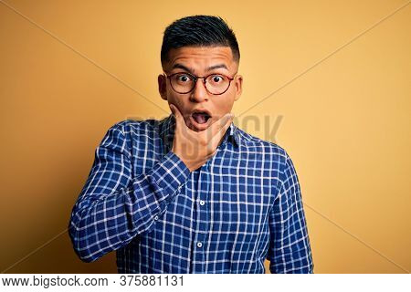 Young handsome latin man wearing casual shirt and glasses over yellow background Looking fascinated with disbelief, surprise and amazed expression with hands on chin