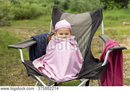 A Little Girl Sitting On A Deck Chair In A Pink Towel And Froze