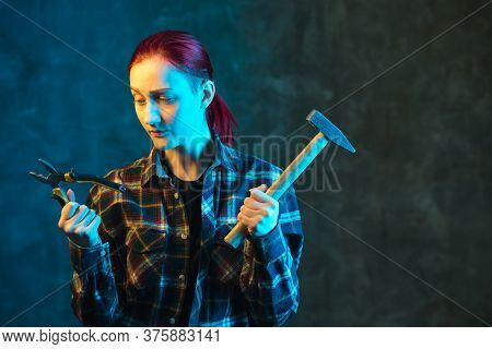 Girl Builder Holds Hammer And Pliers In His Hand. Young Woman In Plaid Shirt With Neon Light. Incomp