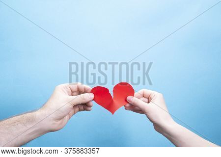 Female And Male Hand Break A Paper Red Heart On A Blue Background With Place For Text. Relationship