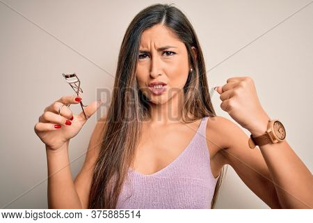 Young beautiful brunette woman holding eyelash curler over isolated white background annoyed and frustrated shouting with anger, crazy and yelling with raised hand, anger concept