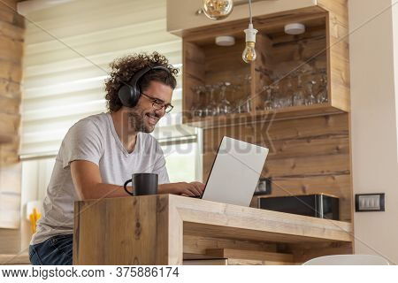 Man Sitting At The Kitchen Counter, Working On Laptop Computer, Telecommuting; Male Freelancer Worki