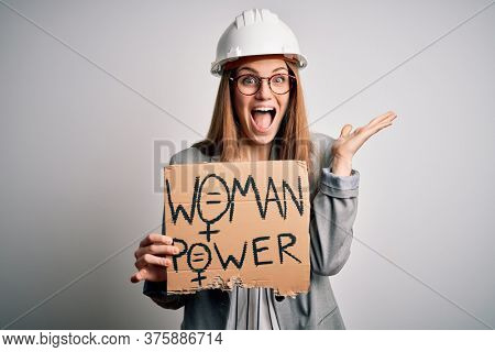 Young redhead architect asking for women rights holding banner with woman power message very happy and excited, winner expression celebrating victory screaming with big smile and raised hands