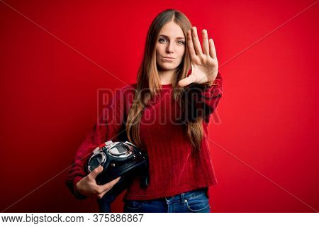 Young beautiful redhead motocyclist woman holding moto helmet over red background with open hand doing stop sign with serious and confident expression, defense gesture