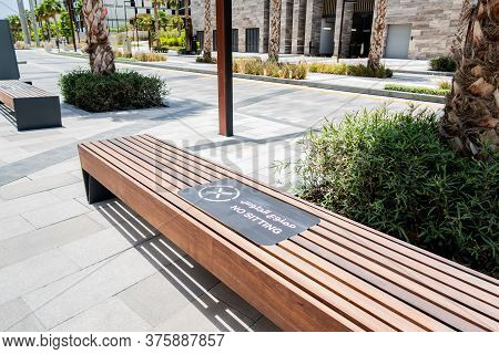 Dubai, Uae. Brown Wooden Bench Forbidden To Sit With No Sitting Sign In Arabic And English, Safety P