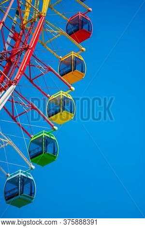 A Big Colourful Ferris Wheel Isolated On Blue Sky Background In Amusement Park. Summer Family Vacati