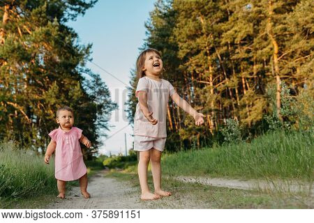 Two Little Sisters Of Caucasian Appearance Play And Run Barefoot In Nature. Concept - Friendliness A