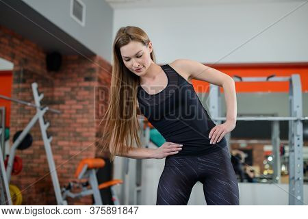 Portrait Of Fitness Woman Stretching At Gym Before Workout. Sports Activity, Healthy Lifestyle. Side