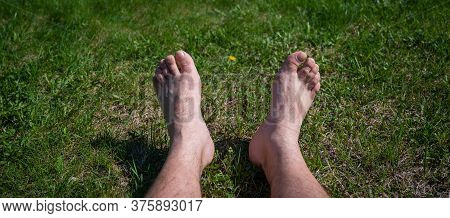 Male Bare Feet On A Lawn In A Park On A Hot Sunny Summer Day. A Man Lies On The Grass Green Grass Wi