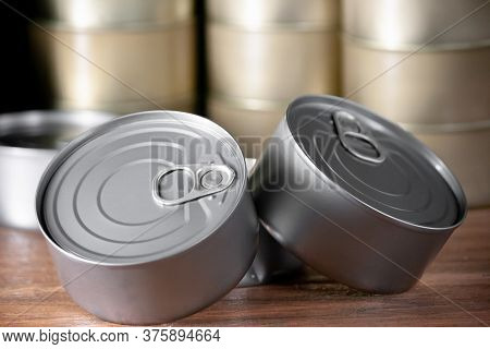 Cans Of Silver Colored Tuna In A Close Up View And Background With Many Cans Of Tuna On Brown Wood