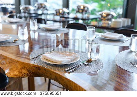 Tableware Setting In The Restaurant. Decorated Elegant Table, Porcelain Plates, Glasses, Napkin, Kni