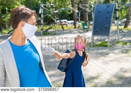 A Girl In A Protective Mask Drags Her Mother To The Playground. Naughty Moody Kid Wants To Play. Qua