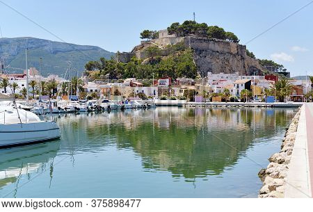 Waterside View To Moored Yachts At Harbour, Old Famous Denia Castle Located On Rocky Hilltop Mountai