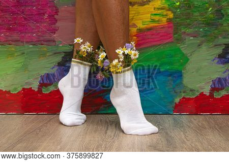 Female Legs With Fresh Flowers In Socks. A Hipster Girl With Flowers From White Socks On Colorful Ba