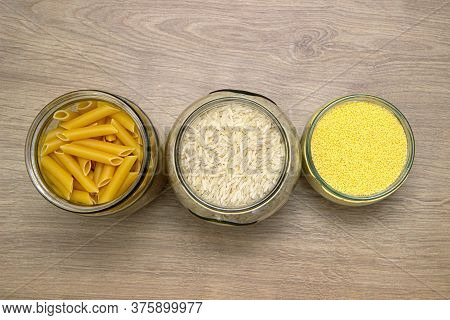 Assortment Of Uncooked Cereals And Pasta In Glass Jars On Wooden Table. Healthy Cooking, Clean Eatin