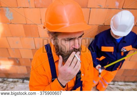 Builder Man Construction Worker Smoking Cigarette. Foreman In Safety Helmet And Overalls Smoking Cig