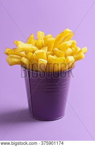Bucket Of French Fries Isolated On Purple Seamless Background. Golden Deep-fried Potatoes In A Purpl