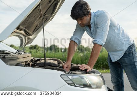 Man Standing Next To A Broke Down Car, Looking Down At Engine In Frustration